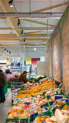 Customers looking at vegetables by the light of Philips fresh food lighting
