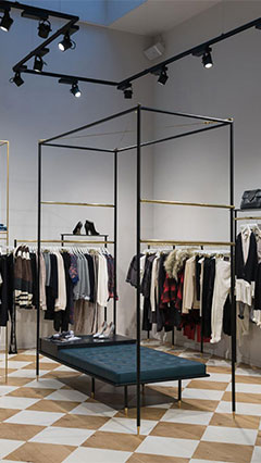 Merchandise hangs on racks at SuperTrash, illuminated by Philips retail lighting