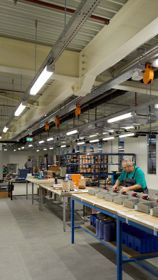 An employee works at the Venco Campus production area, lit brightly thanks to Philips industrial lighting