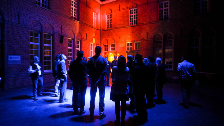 A big group of people is discussing outside of a nicely lit building at Turnhout, Belgium in a workshop organized by Philips