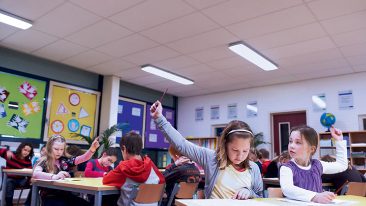 Children engrossed in a lesson raise their hands to answer a question from a teacher - optimum learning environment